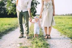 Familj p? naturen Moder och fader med att behandla som ett barn utomhus arkivbild