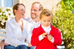 Familj på trädgårds- bänk framme av hemmet Royaltyfri Bild