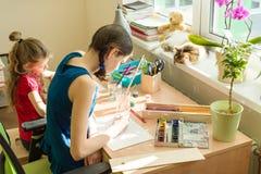 Familj rekreation, kreativitet, hem Flickasystrar hemma på tabellmålarfärgen med vattenfärgen arkivbild