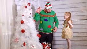 Familj runt om en julgran som dekorerar den arkivfilmer