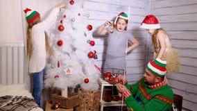 Familj runt om en julgran som dekorerar den Arkivbilder