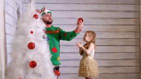 Familj runt om en julgran som dekorerar den Fotografering för Bildbyråer
