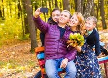 Familj, säsong, teknologi och folkbegrepp - den lyckliga familjen som tar selfie vid smartphonen i autumnl, parkerar arkivbilder