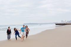Familj som är skämtsam tillsammans på stranden Royaltyfria Bilder