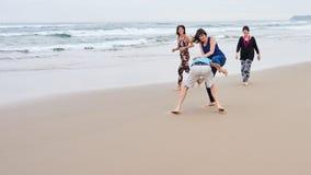 Familj som är skämtsam tillsammans på stranden Fotografering för Bildbyråer