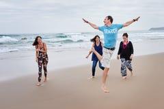 Familj som är skämtsam tillsammans på stranden Royaltyfria Foton