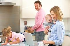 Familj som är upptagen tillsammans i kök arkivbilder