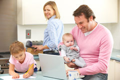 Familj som är upptagen tillsammans i kök royaltyfri fotografi