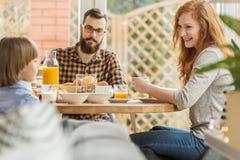 Familj som äter frukosten i axel arkivbild