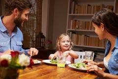 Familj som äter matställen på en äta middag tabell arkivbilder