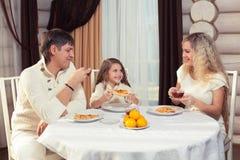 Familj som äter matställen på en äta middag tabell, rund tabell, pizza, apelsin, hus som göras av trä Arkivfoto