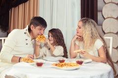 Familj som äter matställen på en äta middag tabell, rund tabell, pizza, apelsin, hus som göras av trä arkivfoton