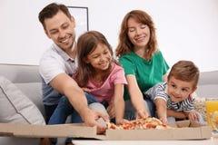 Familj som äter pizza, medan hålla ögonen på TV royaltyfria foton