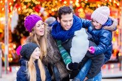 Familj som äter sockervadden på julmarknad royaltyfria bilder
