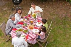 Familj som äter utanför i trädgården Royaltyfri Fotografi