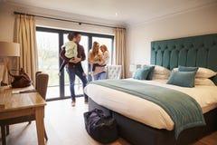 Familj som ankommer i hotellrum på semester Fotografering för Bildbyråer