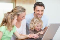 Familj som använder anteckningsboken i kök Arkivbild
