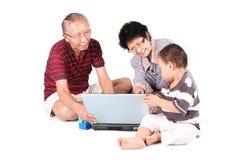 Familj som använder bärbara datorn i studio Fotografering för Bildbyråer