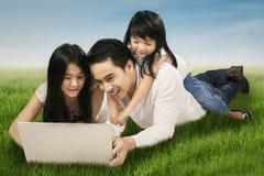 Familj som använder bärbara datorn på ängen Arkivfoton