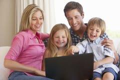 Familj som använder bärbara datorn på Sofa At Home Royaltyfri Bild