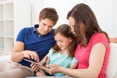 Familj som använder den digitala minnestavlan på soffan Arkivbild