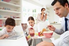 Familj som använder Digital apparater på frukosttabellen Arkivfoto