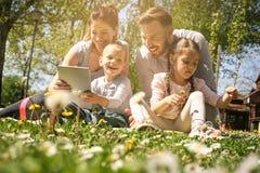 Familj som använder digitalt minnestavlasammanträde på det gröna gräset Fa royaltyfria bilder