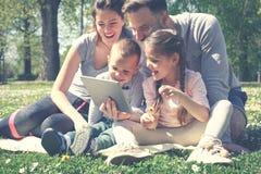 Familj som använder digitalt minnestavlasammanträde på det gröna gräset Fa royaltyfri bild