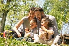 Familj som använder minnestavlan arkivbilder