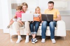 Familj som använder minnestavlor och datorer royaltyfri foto