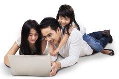Familj som använder bärbara datorn på golvet Arkivbilder