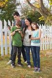 Familj som använder mobiltelefoner Fotografering för Bildbyråer