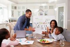 Familj som applåderar på ett inhemskt möte i deras kök royaltyfri bild