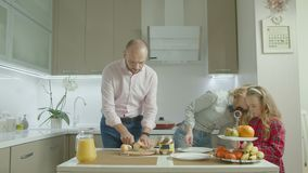 Familj som applicerar jordnötsmör på rostat bröd i kök lager videofilmer