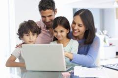 Familj som arbetar på bärbara datorn med i inrikesdepartementet Royaltyfria Foton