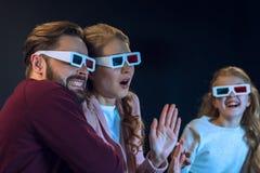 Familj som bär exponeringsglas som 3d tillsammans håller ögonen på film Arkivfoton