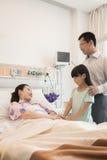 Familj som besöker modern i sjukhuset som rymmer händer royaltyfria foton