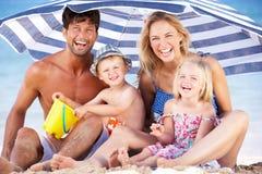Familj som beskyddar från Sun under strandparaplyet Arkivbild