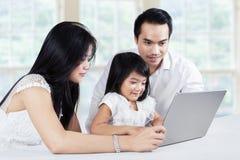 Familj som bläddrar internet med bärbara datorn på tabellen Arkivbild