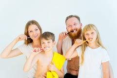 Familj som borstar tänder Fotografering för Bildbyråer