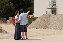 Familj som bygger ett hus - fastighet Arkivfoto