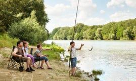 Familj som campar och fiskar, flod och skog, sommarsäsong Royaltyfria Bilder
