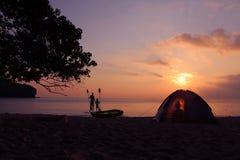 Familj som campar på stranden med kayaking aktivitet Fotografering för Bildbyråer