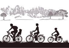 Familj som cyklar i bygd Arkivfoton