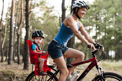 Familj som cyklar i skogen Arkivfoton