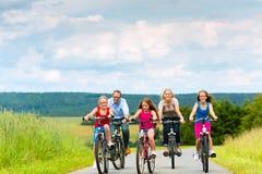 Familj som cyklar i sommar i lantligt landskap Royaltyfri Fotografi