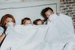 Familj som döljer under filten som håller ögonen på den läskiga filmen royaltyfria foton