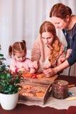 Familj som dekorerar bakade julpepparkakakakor arkivbild
