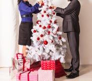 Familj som dekorerar en julgran i uppehället fotografering för bildbyråer