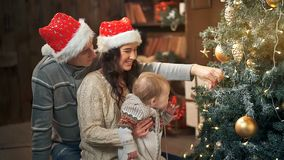 Familj som dekorerar en julgran med bollar i vardagsrummet lager videofilmer